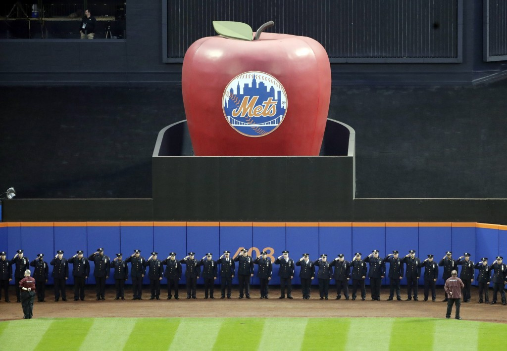 Members of the New York Police Department salute during the pregame ceremony of a baseball game between the New York Mets and the Miami Marlins, Tuesd