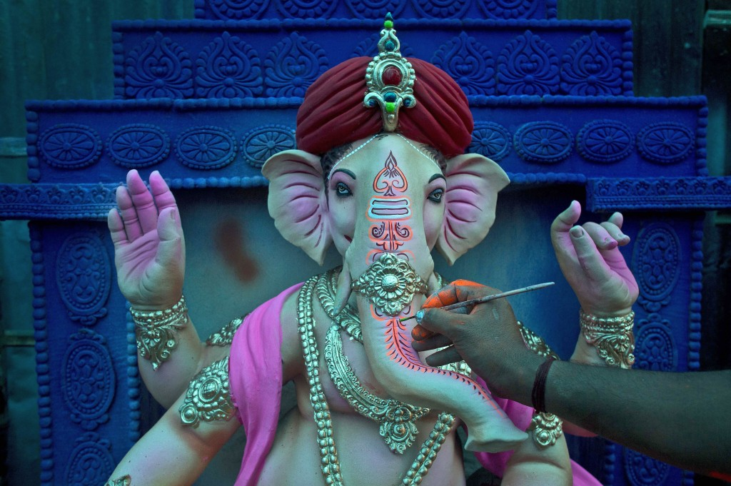 In this Wednesday, Sept. 12, 2018, file photo, an artisan puts final touches on an idol of Hindu God Ganesha ahead of Ganesha Chaturthi at a workshop