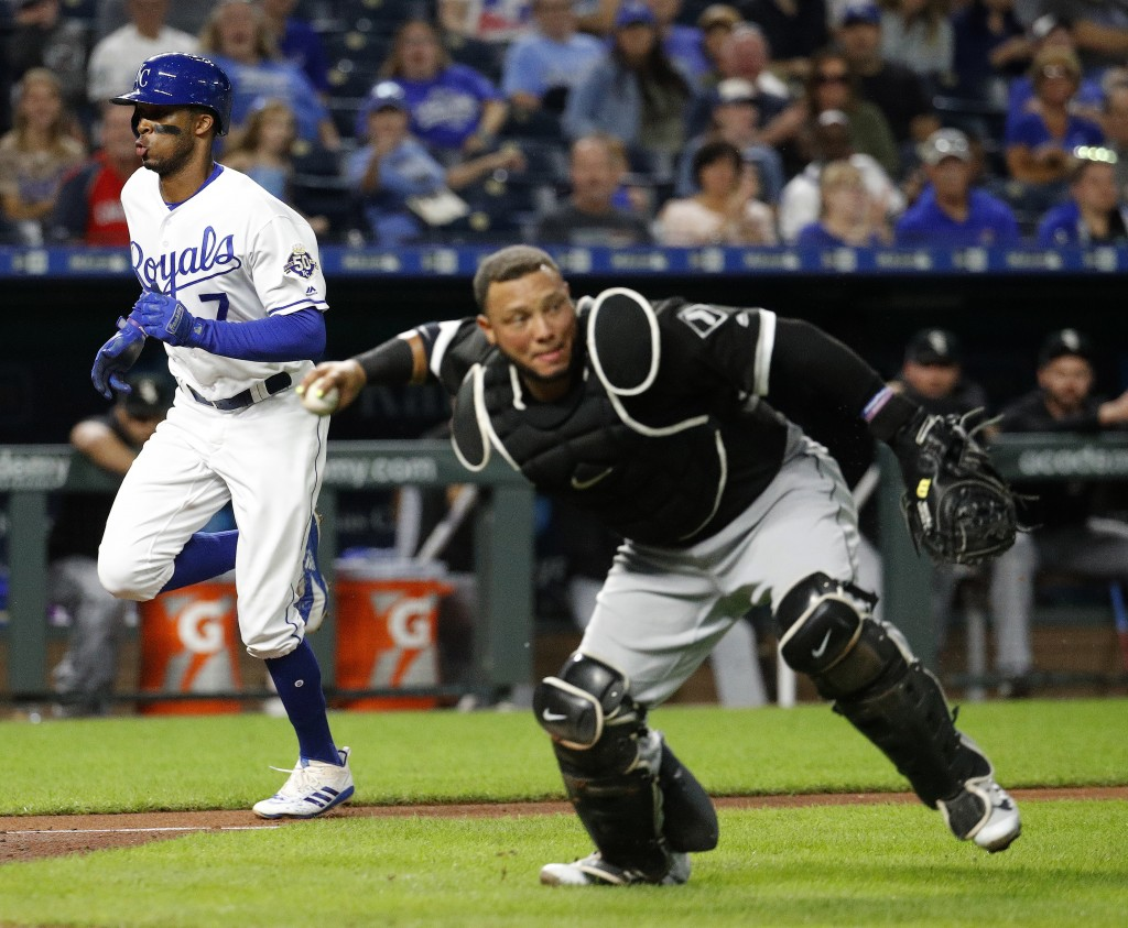 Chicago White Sox catcher Welington Castillo throws to first after fielding a single bunt by Kansas City Royals' Adalberto Mondesi while Rosell Herrer