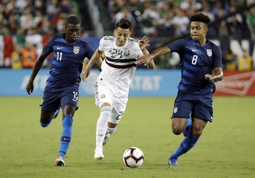 Mexico midfielder Roberto Alvarado (24) dribbles the ball past U.S. midfielders Tim Weah (11) and Weston McKennie (8) during an international friendly