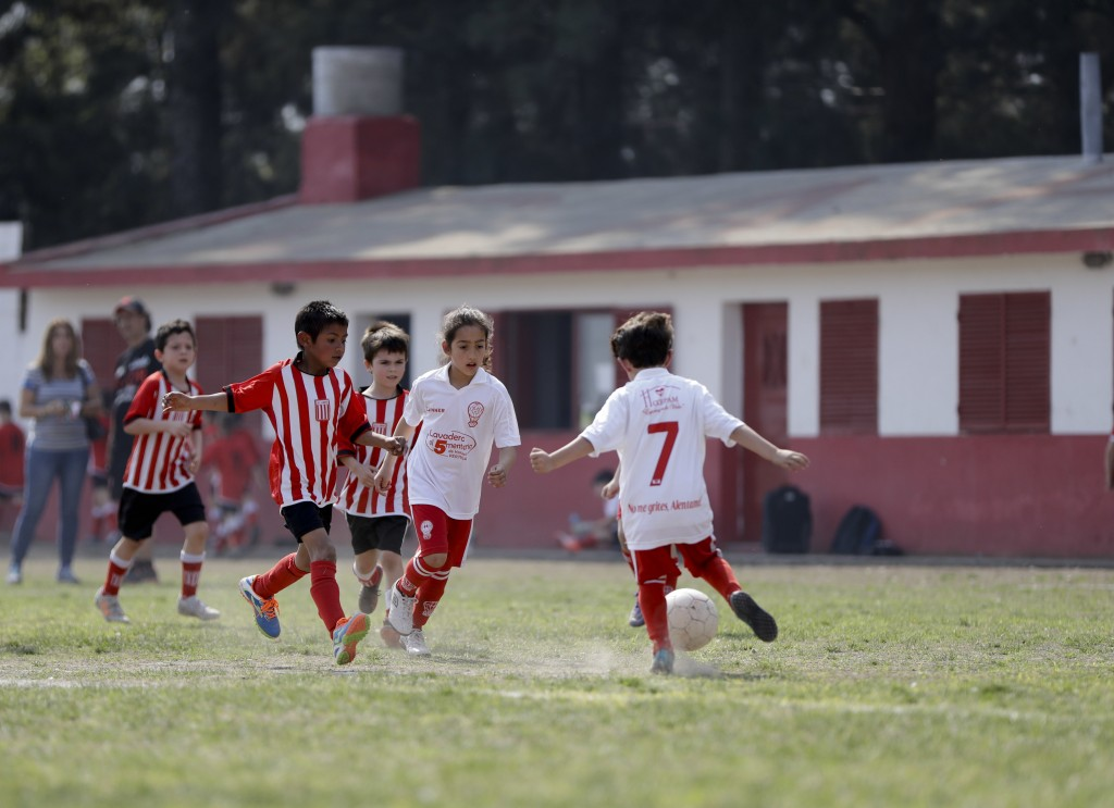 In this Sept. 8, 2018 photo Candelaria Cabrera, center, plays with her soccer teammates against the Alumni Club, in Chabaz, Argentina. While she's off