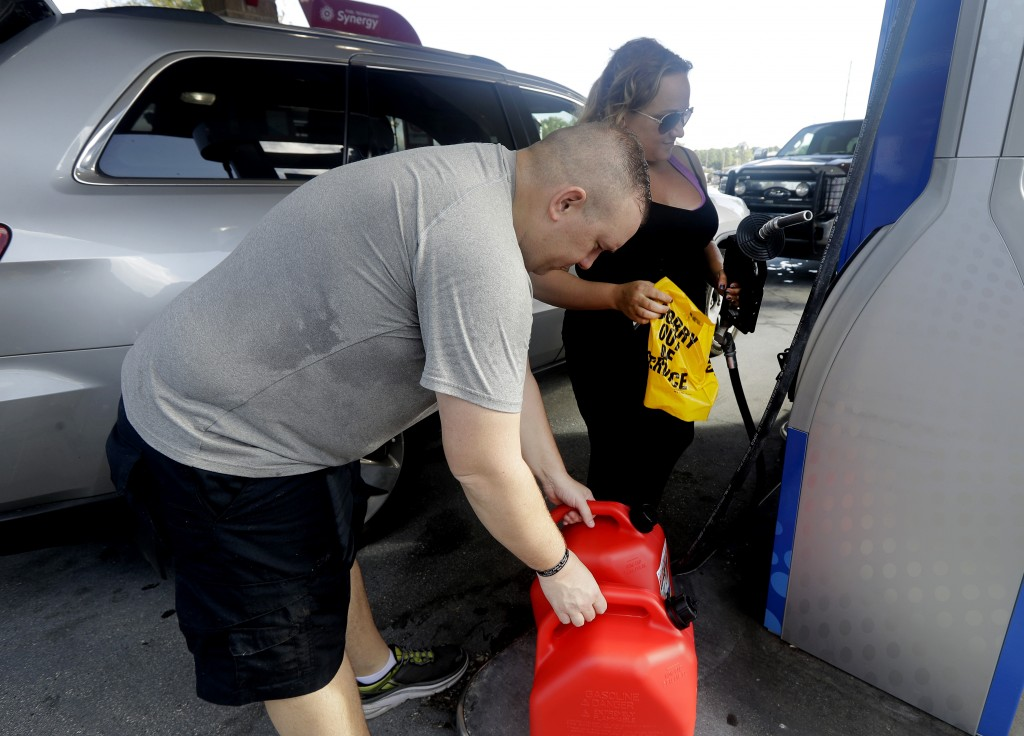"Sarah Dankanich, right, removes an ""out of service"" wrapper from a gas pump as her husband, Bryan Dankanich, left, prepares to pump gas in cans in adv"