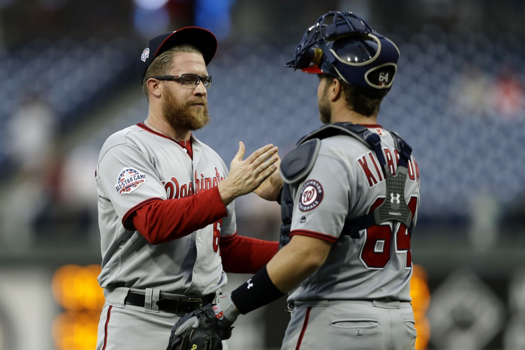 Washington Nationals relief pitcher Sean Doolittle, left, and catcher Spencer Kieboom celebrate after winning the first game of a baseball doubleheade