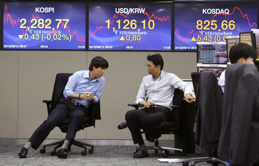 Currency traders talk to each other at the foreign exchange dealing room of the KEB Hana Bank headquarters in Seoul, South Korea, Wednesday, Sept. 12,