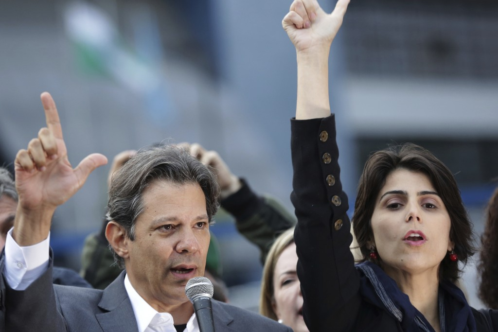 Workers' Party presidential candidate Fernando Haddad, left, and his running-mate Manuela d'Avila hold a campaign rally outside federal police headqua