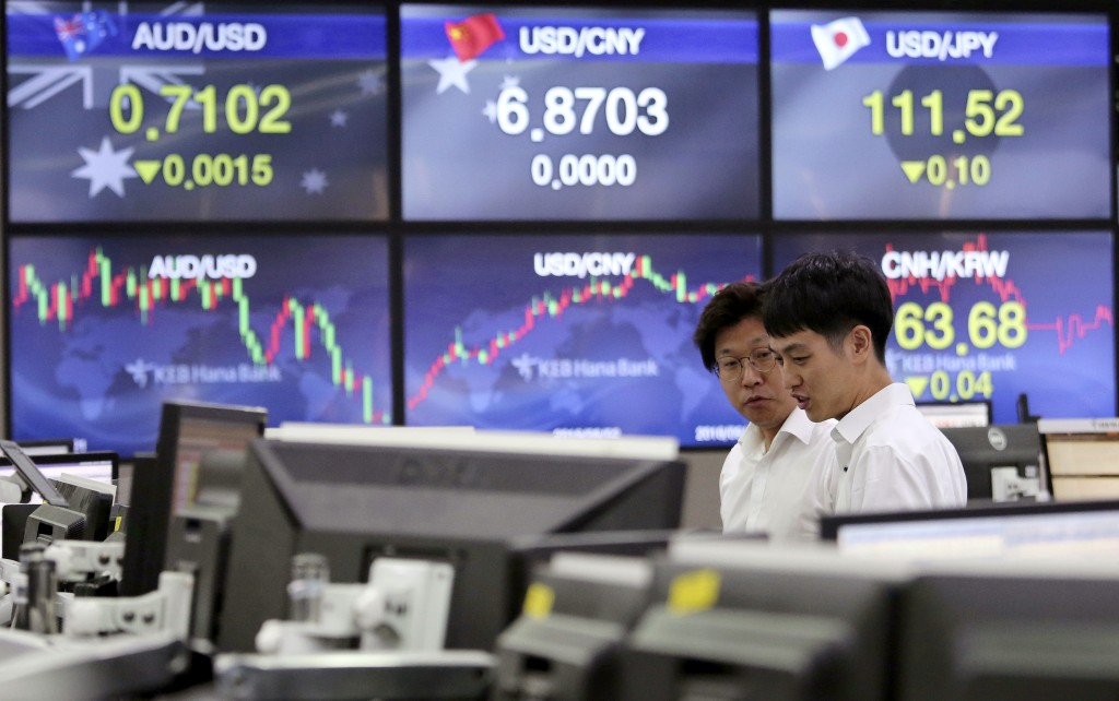 Currency traders watch monitors at the foreign exchange dealing room of the KEB Hana Bank headquarters in Seoul, South Korea, Wednesday, Sept. 12, 201