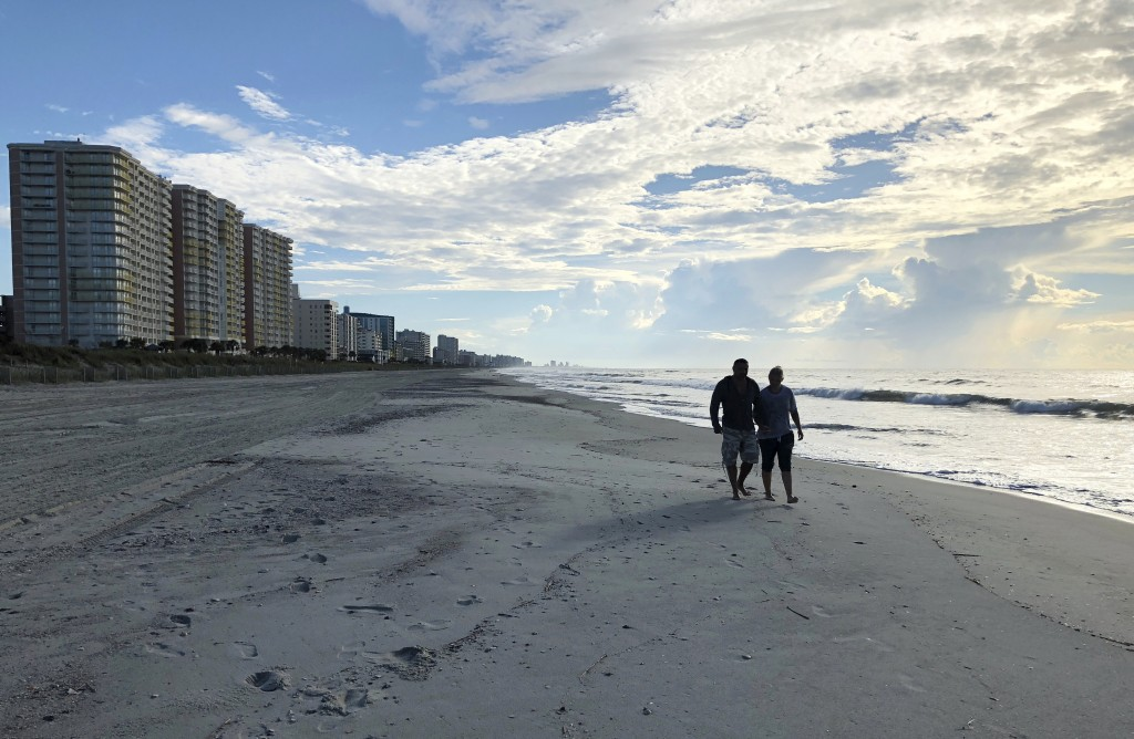 Chris and Nicole Roland walk down a beach in North Myrtle Beach, S.C. on Wednesday, Sept. 12, 2018. The couple boarded up their uncle's condominium an
