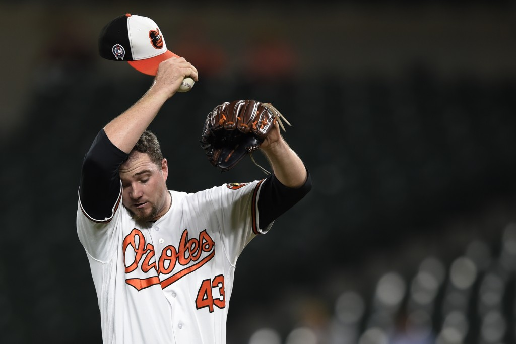 Baltimore Orioles pitcher Mike Wright Jr. wipes his face after the Oakland Athletics score three runs in the third inning of a baseball game, Tuesday,