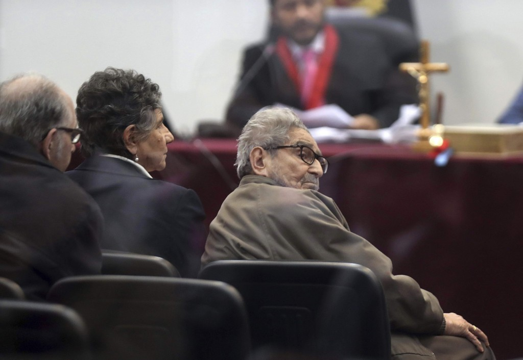 In this photo taken through a window, Abimael Guzman, founder and leader of the Shining Path guerrilla movement, looks at his lawyer while siting with