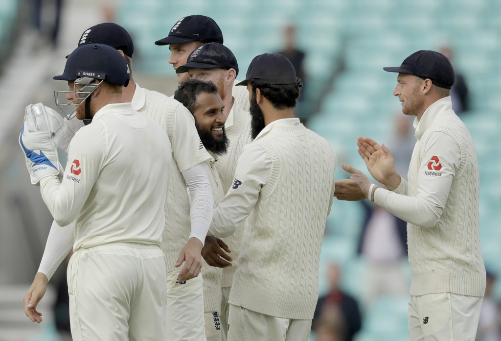 England's Adil Rashid, center, celebrates taking the wicket of India wicketkeeper Rishabh Pant for 114 runs during the fifth cricket test match of a f