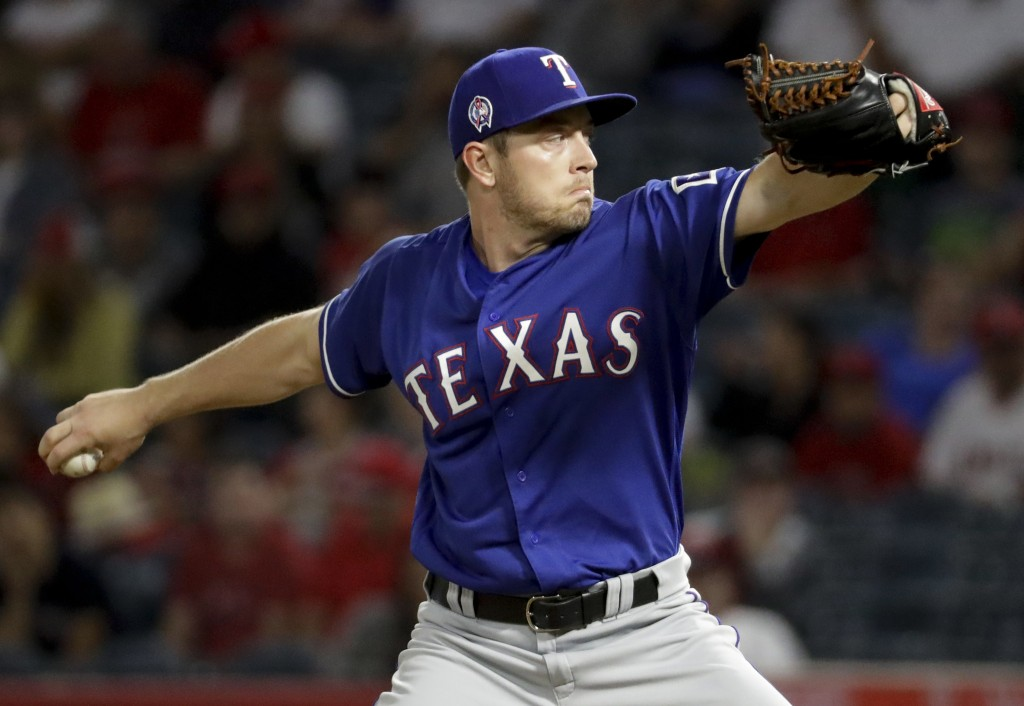 Texas Rangers starting pitcher Adrian Sampson throws against the Los Angeles Angels during the first inning of a baseball game in Anaheim, Calif., Tue