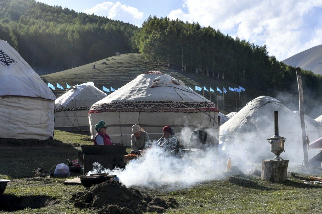 In this photo taken on Saturday, Sept. 1, 2018, family members cook traditional food, during the Third Nomad Games, in Cholpon-Ata, 250 kilometers (15...