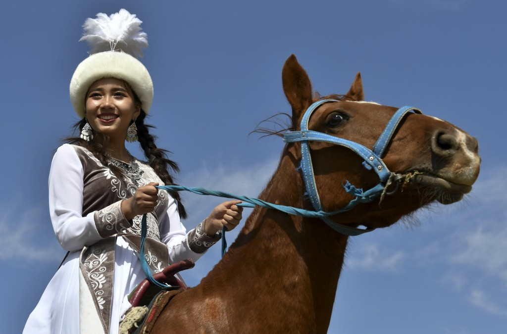 In this photo taken on Thursday, Sept. 6, 2018, a Kyrgyz woman, a participant of a horse-riding competition poses for a photo during the Third Nomad G...