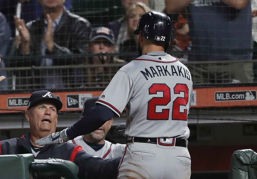 Atlanta Braves' Nick Markakis (22) is congratulated by manager Brian Snitker, left, after scoring a run against the San Francisco Giants on a sacrific