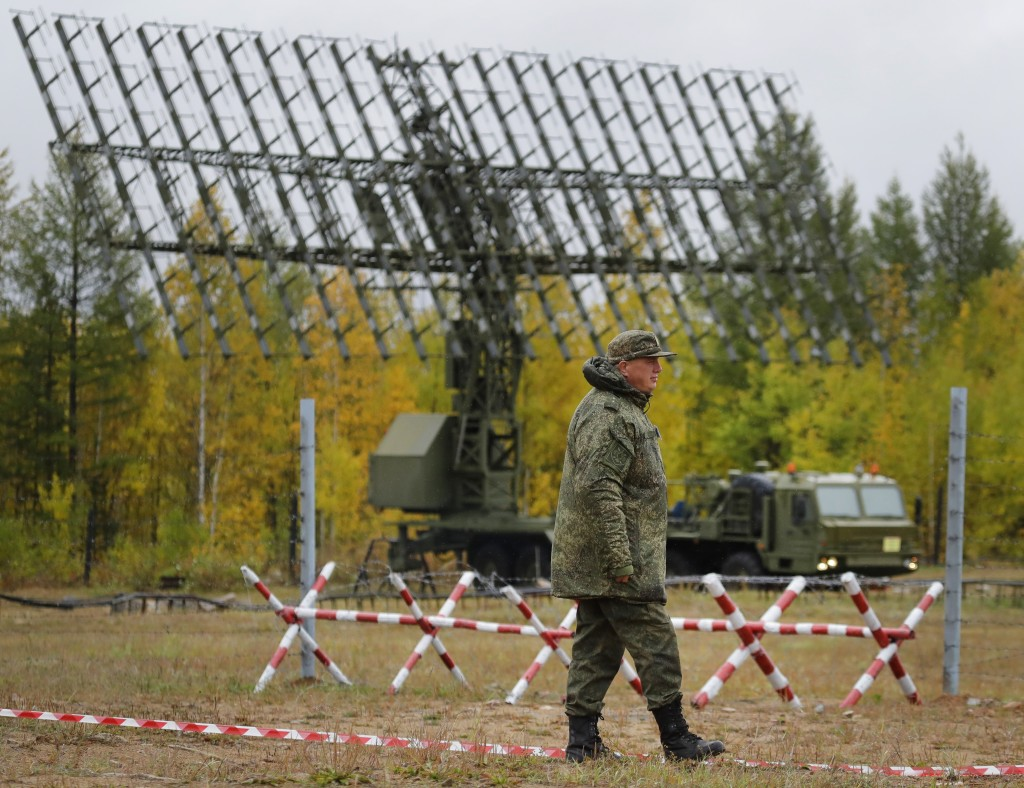 """A Russian walks past a Nebo-M radar deployed in a forest, during a military exercises on training ground """"Telemba"""", about 80 kilometers (50 miles ) no"""