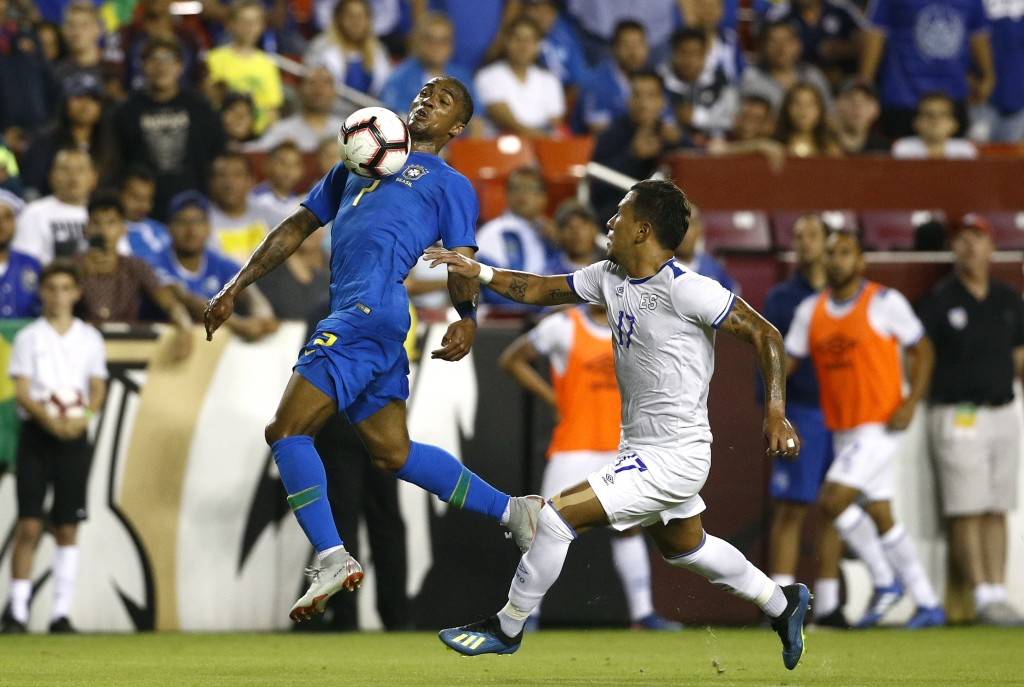 Brazil forward Douglas Costa, left, tries to maintain possession as he is pressured by El Salvador defender Juan Barahona in the first half of a socce...