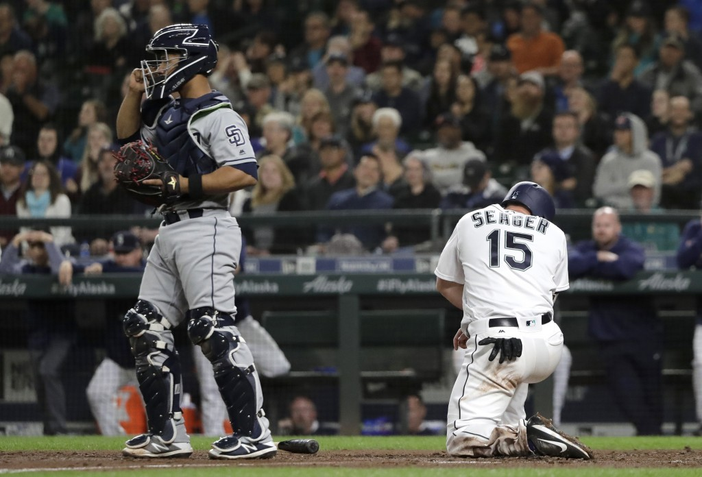 Seattle Mariners' Kyle Seager kneels at the plate after he was tagged out at home by San Diego Padres catcher Francisco Mejia, left, on a fielders cho