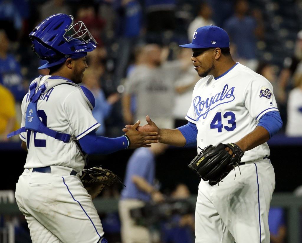Kansas City Royals catcher Meibrys Viloria and relief pitcher Wily Peralta (43) celebrate after their baseball game against the Chicago White Sox Tues