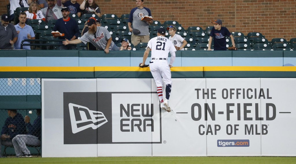 Detroit Tigers left fielder JaCoby Jones climbs the outfield wall but can't reach a Houston Astros' Tyler White two-run home run in the fourth inning