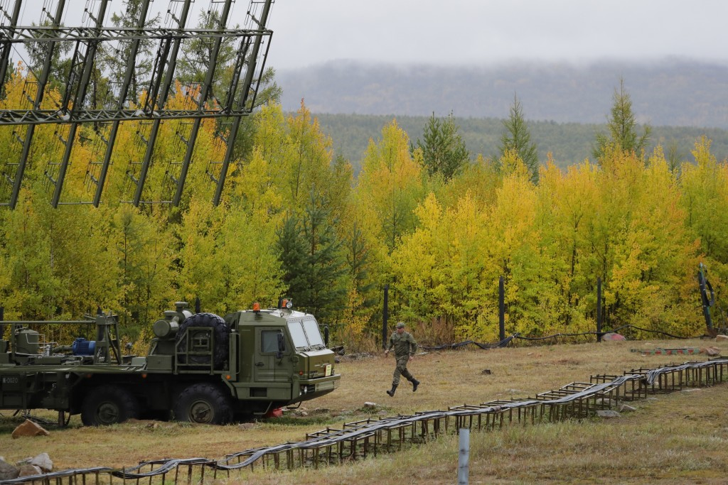 """A Russian soldier runs towards a Nebo-M radar deployed by a forest, during a military exercises on training ground """"Telemba"""", about 80 kilometers (50"""