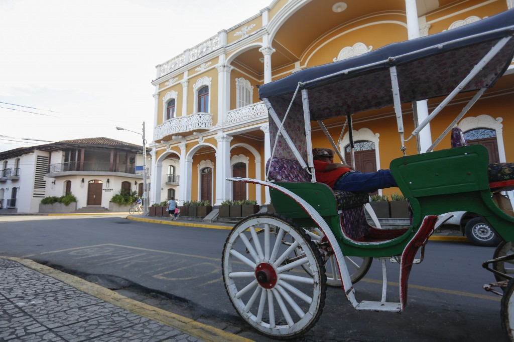 A coach driver takes a nap as he waits for tourists in the colonial city of Granada, Nicaragua, Monday, Sept. 10, 2018. The U.S., Canada, Spain and En