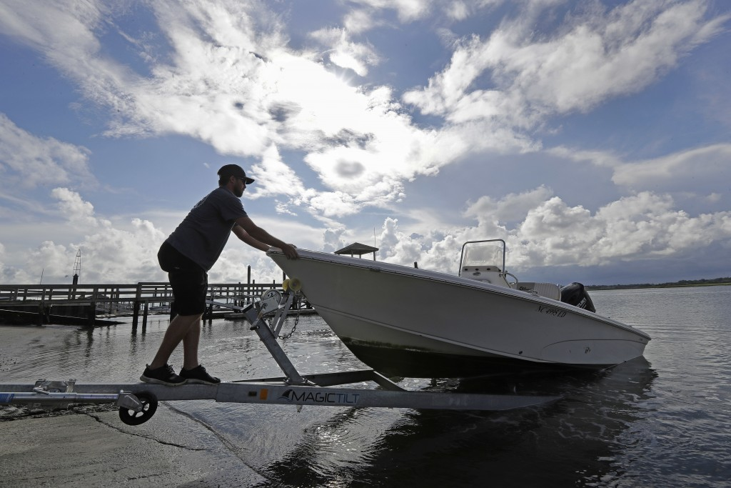 Nick Hobbs, of Marine Warehouse Center, removes a customer's boat from the water in advance of Hurricane Florence in Wrightsville Beach, N.C., Tuesday