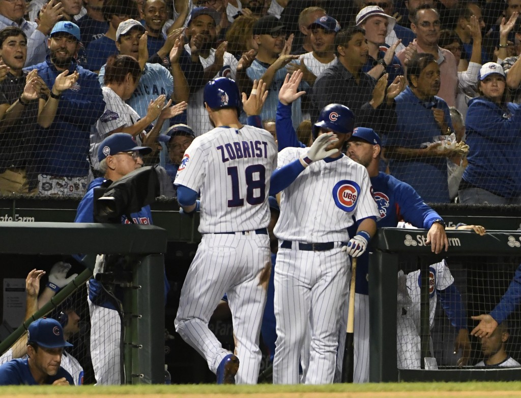 Chicago Cubs' Ben Zobrist (18) is greeted by his teammates after scoring against the Milwaukee Brewers during the second inning of a baseball game, Tu