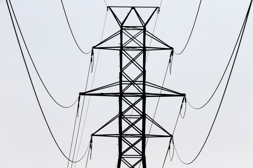 FILE- In this Aug. 14, 2018, file photo power transmission lines carry electricity along the Interstates 40 and I-85 corridor in Orange County near Hi...