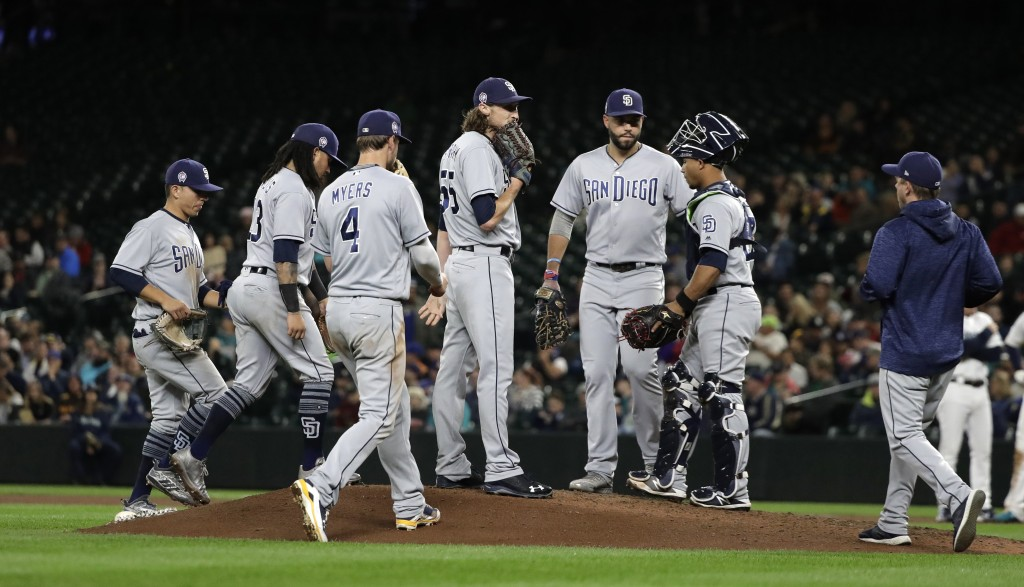 San Diego Padres relief pitcher Matt Strahm, center, stands on the mound and awaits a visit from Padres pitching coach Darren Balsley, right, during t