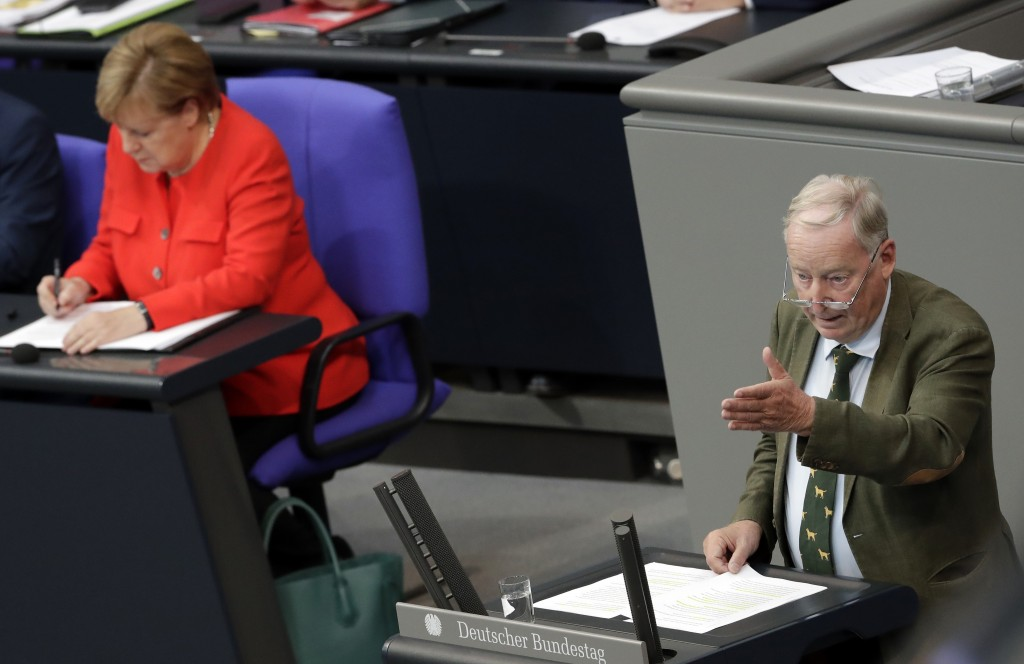 German Chancellor Angela Merkel, left, writes as she attends the speech of Alexander Gauland, co-faction leader of the Alternative for Germany party,