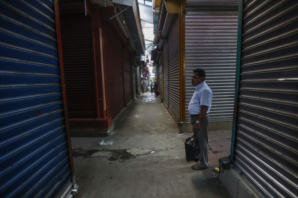 In this Sept 7, 2018 photo, a man walks in the empty and shuttered halls of the Oriental Market during a 24 hour national strike, in Managua, Nicaragu