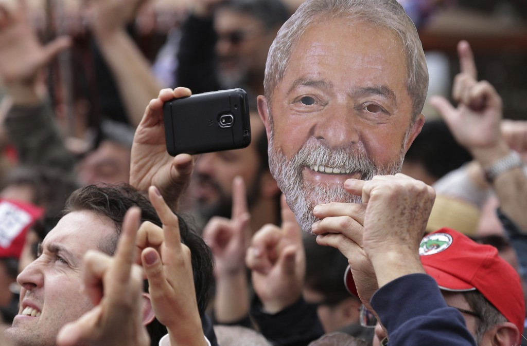 A supporter holds a mask in the likeness of the Brazil's jailed former President Luiz Inacio Lula da Silva, during a campaign rally outside federal po
