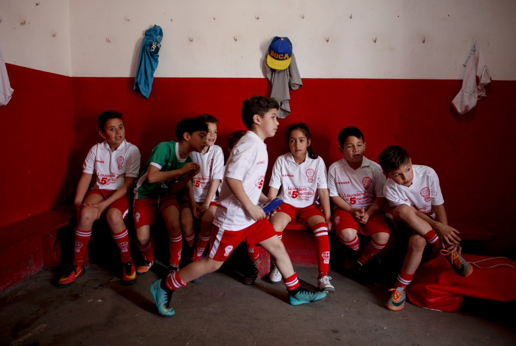 In this Sept. 8, 2018 photo, Candelaria Cabrera, third from right, sits with her teammates before a match against the Alumni soccer team, in Chabaz, A