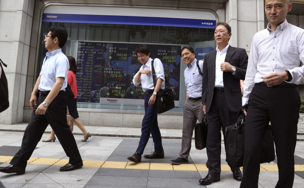 In this Sept. 11, 2018, photo, people walk by an electronic stock board of a securities firm in Tokyo. Asian shares fell on Wednesday, Sept. 12, as Ch