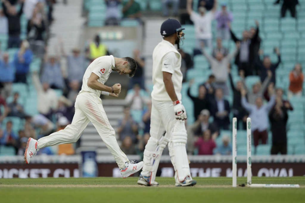 England's Jimmy Anderson celebrates taking the wicket of India's Mohammed Shami, right, for the most number of wickets ever taken by a pace bowler dur