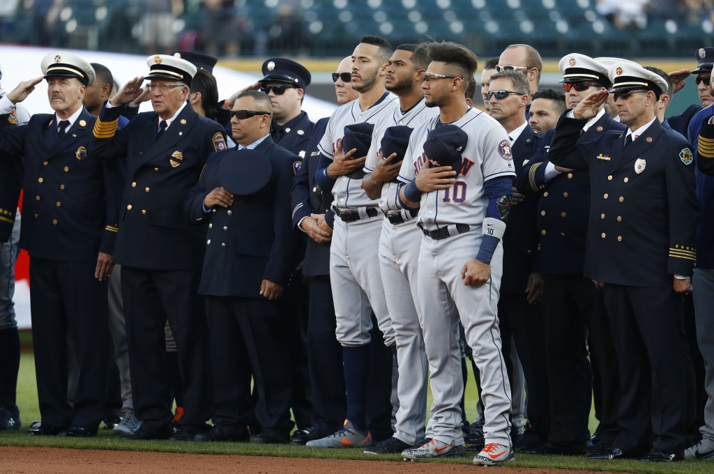 Houston Astros' Carlos Correa, from left, Josh James and Yuli Gurriel (10) stand with first responders during the national anthem before a baseball ga