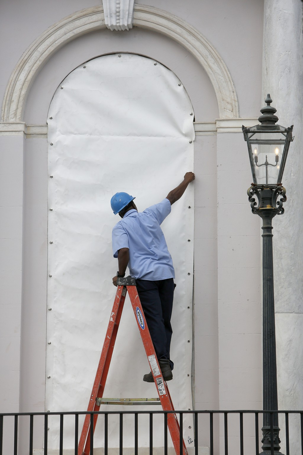 A worker covers a window at Charleston City Hall in Charleston, S.C., in preparation for the advancing Hurricane Florence Tuesday, Sept. 11, 2018. (AP