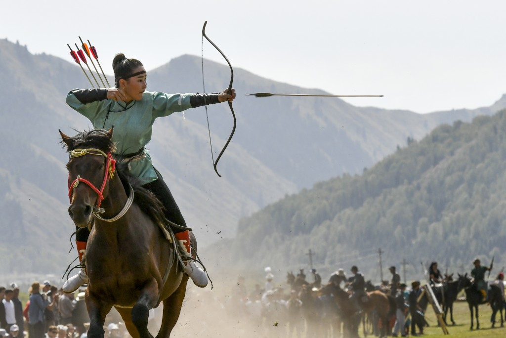 In this photo taken on Thursday, Sept. 6, 2018, a women releases an arrow during an archery competition during the Third Nomad Games, in Cholpon-Ata, ...