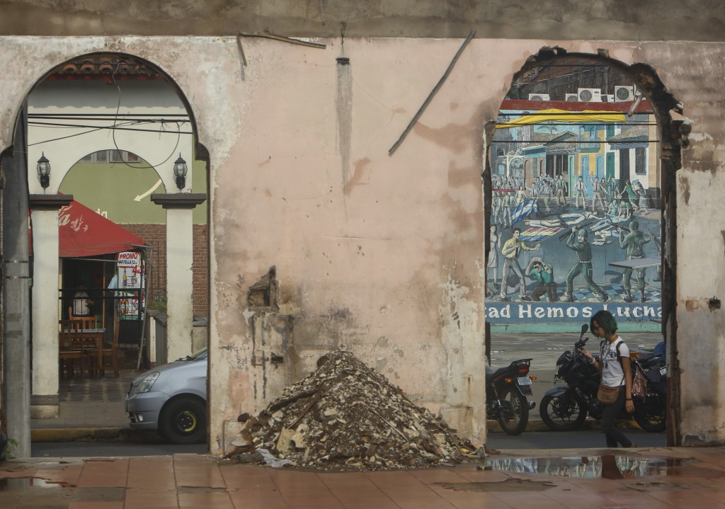 A woman walks past the gutted remains of Nicaragua's National University building in Leon, Nicaragua, Tuesday, Sept. 11, 2018. The university building