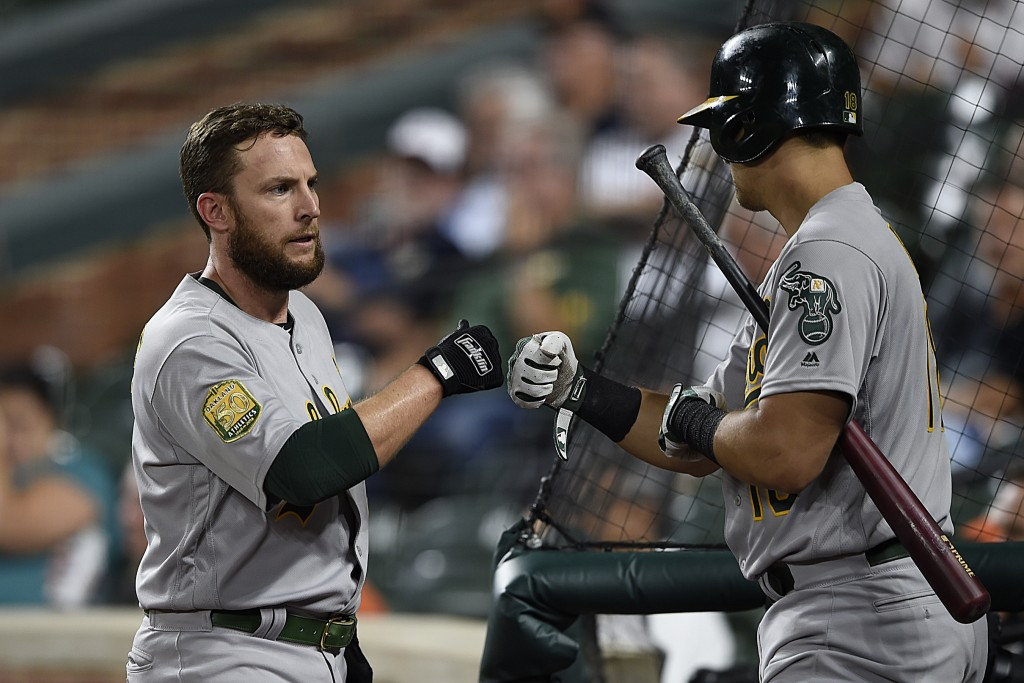 Oakland Athletics' Jed Lowrie, left, is congratulated by Chad Pinder after scoring against the Baltimore Orioles in the third inning of a baseball gam