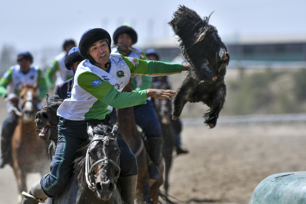 In this photo taken on Wednesday, Sept. 5, 2018, horse riders compete for the goat during a kok boru, also called ulak tartysh match between France an