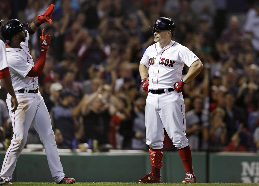 Boston Red Sox's Brock Holt, right, poses as Eduardo Nunez, left, pretends to shoot his picture after crossing home plate following his pinch-hit, thr