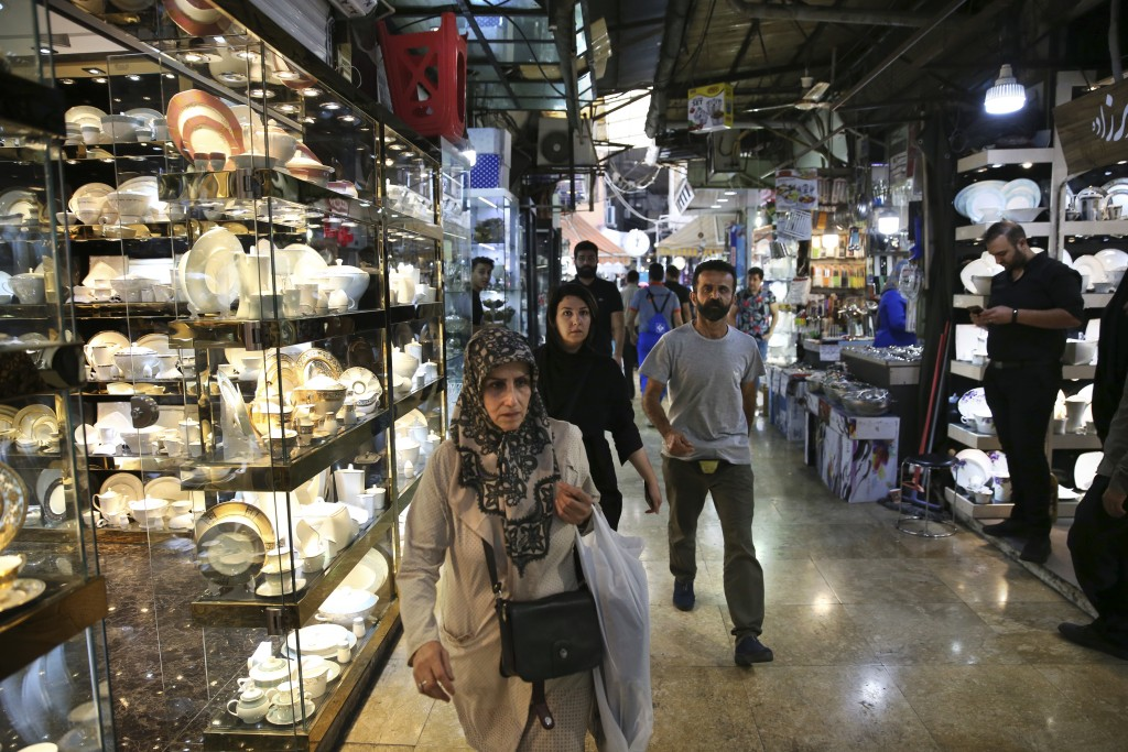 In this Thursday, Sept. 6, 2018, photo, people walk through the Grand Bazaar where Chinese-made goods have flooded the market, in Tehran, Iran. It's h