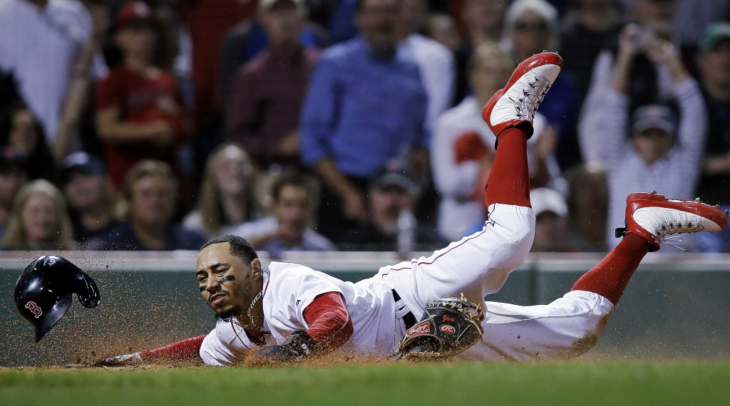Boston Red Sox's Mookie Betts scores on a double by Andrew Benintendi during the eighth inning of a baseball game against the Toronto Blue Jays at Fen