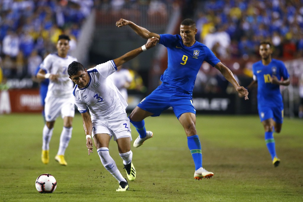 El Salvador defender Roberto Dominguez, left, chases after the ball alongside Brazil forward Richarlison in the first half of a soccer match, Tuesday,