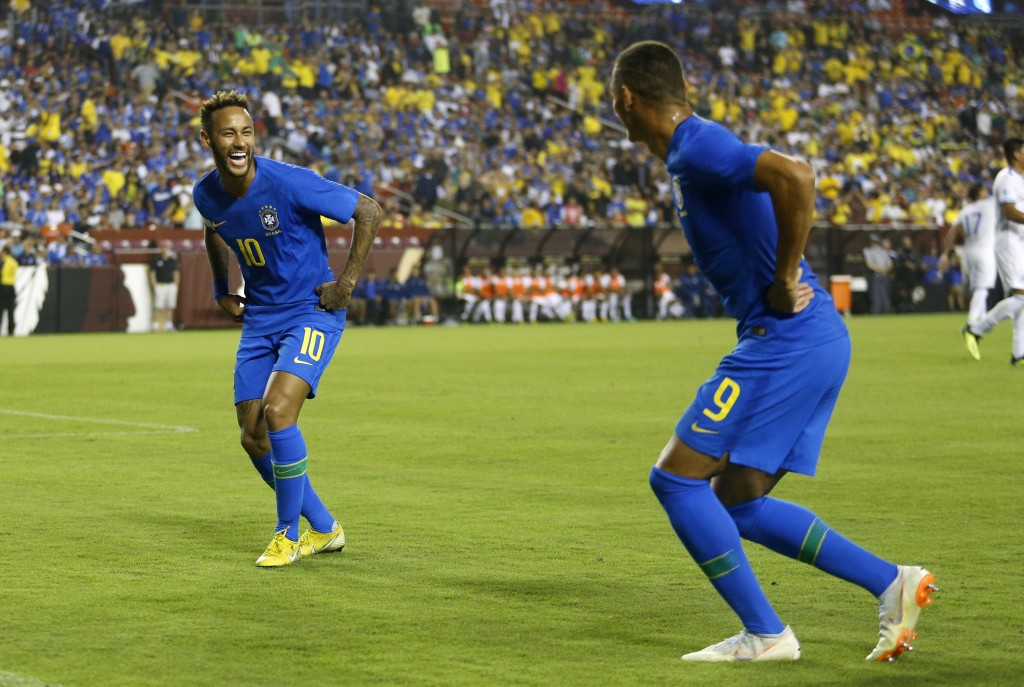 Brazil forward Neymar, left, celebrates with teammate Richarlison after Richarlison scored a goal in the first half of a soccer match against El Salva...