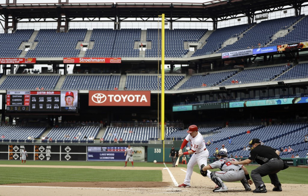 Philadelphia Phillies' Justin Bour, left, hits a double off Washington Nationals relief pitcher Erick Fedde during the first inning of the first game