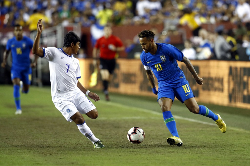 Brazil forward Neymar, right, dribbles the ball around El Salvador midfielder Gilberto Baires in the first half of a soccer match, Tuesday, Sept. 11, ...