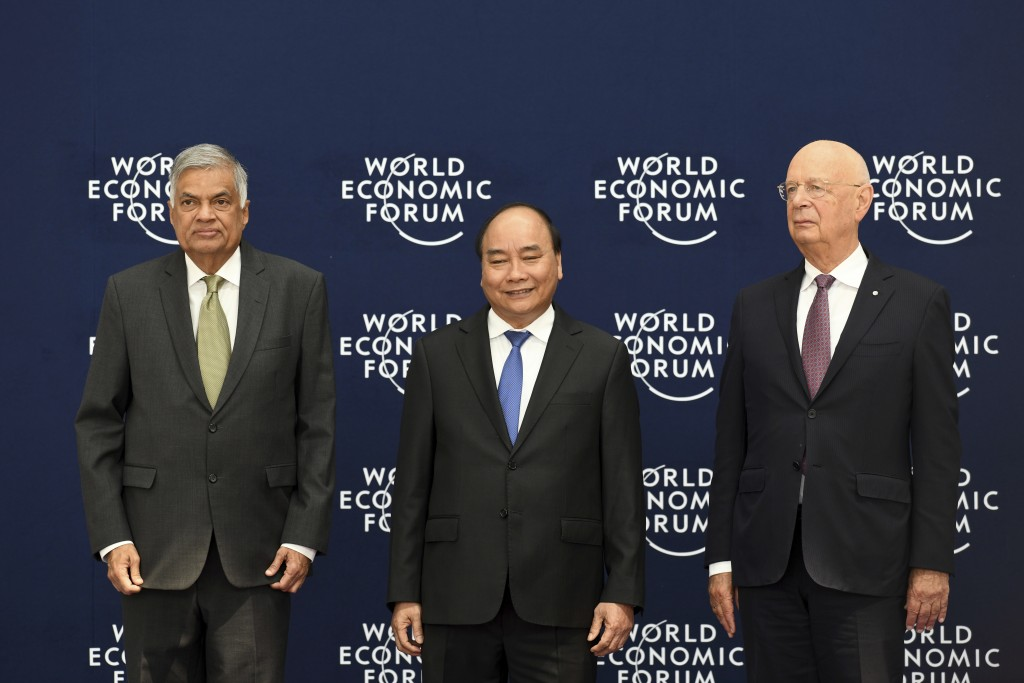 Sri Lankan Prime Minister Ranil Wickremesinghe, left,  Vietnamese Prime Minister Nguyen Xuan Phuc, center, and Klaus Schwab, founder and executive cha