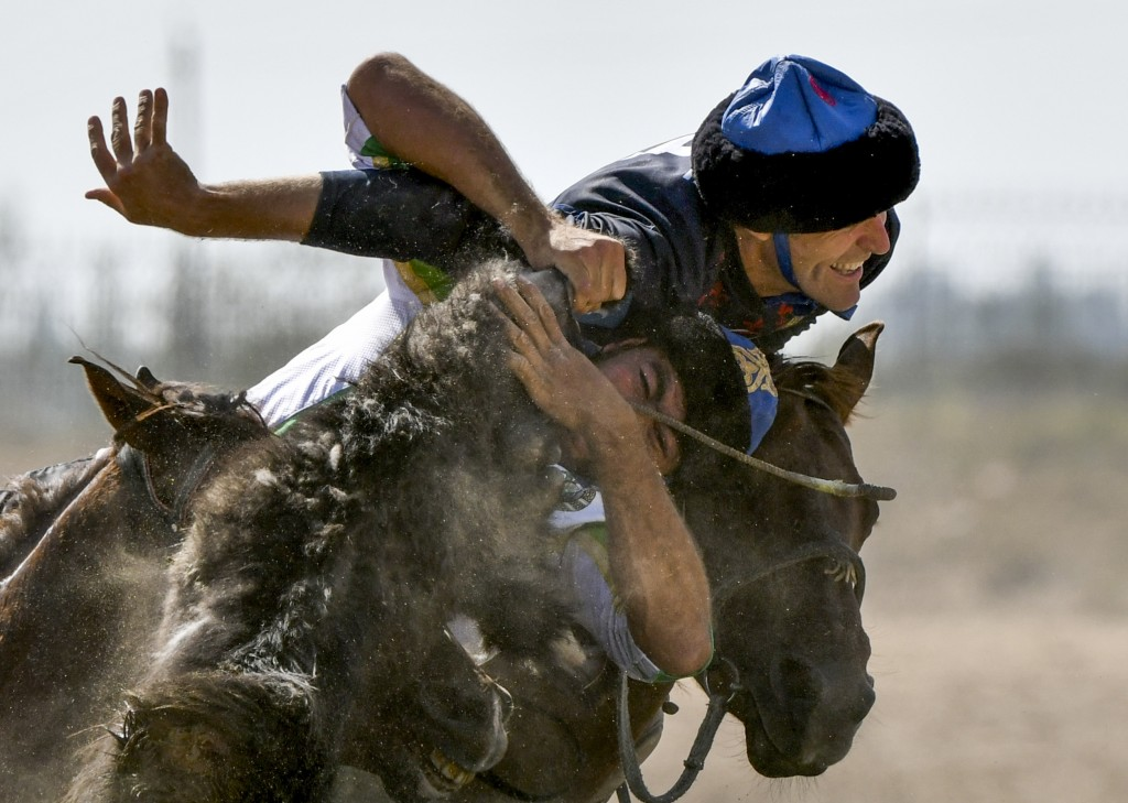 In this photo taken on Wednesday, Sept. 5, 2018, horse riders compete for the goat during a kok boru, also called ulak tartysh match between France an...